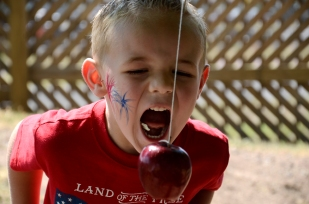 Taryn Ashlosk, 5, tried to get the apple without using his hands at the Hometown Celebration July Fourth at Leonardo's Discovery Warehouse and Adventure Quest. Over 300 people attended the festivities, which ran 10 am. to noon.