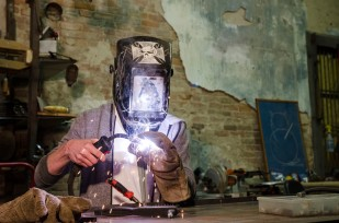 "Seth Ritter, 17, welds a component of his current ""found"" art project. The Lexington high schooler has his own studio in downtown Lexington. A rehabilitated 1850's era store now holds the bits and pieces he gathers to create his art."