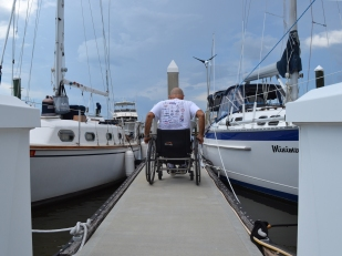 Allen Fiske wheels down Salty Sam's dock to his boat. He's moored at the marina since he moved to the area in 2012.